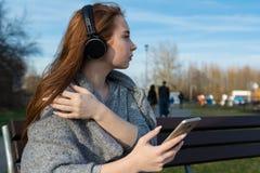 年轻,愉快的红头发人女孩在春天在河附近的公园听到音乐通过无线bluetooth耳机 免版税图库摄影