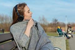 年轻,愉快的红头发人女孩在春天在河附近的公园听到音乐通过无线bluetooth耳机 库存图片