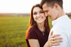 年轻,愉快,爱恋的夫妇,在日落,站立在一个绿色领域,反对天空,在胳膊和开心, advertis 免版税图库摄影