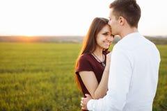 年轻,愉快,爱恋的夫妇,在日落,站立在一个绿色领域,反对天空,在胳膊和开心, advertis 图库摄影