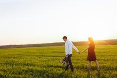 年轻,愉快,爱恋的夫妇,在日落,站立在一个绿色领域,反对握手和开心的天空, adverti 图库摄影