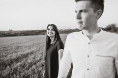年轻,愉快,爱恋的夫妇,在日落,站立在一个绿色领域,反对握手和开心的天空, adverti 库存照片