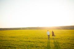 年轻,愉快,爱恋的夫妇,在日落,站立在一个绿色领域,反对握手和开心的天空, adverti 库存图片