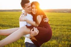 年轻,愉快,爱恋的夫妇,户外,供以人员拿着他的胳膊的一个女孩和开心,给和插入文本做广告 免版税库存照片