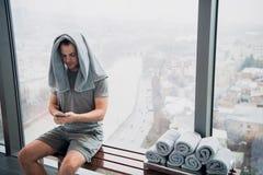 年轻,疲乏的人坐在健身房的长凳 拿着手机和毛巾在他的头 在摩天大楼的健身房有大的 免版税图库摄影