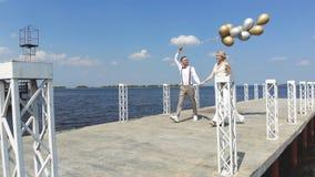 年轻,美丽的夫妇新婚佳偶在美丽的码头在他的手上走,新郎拿着气球,看其中每一 影视素材