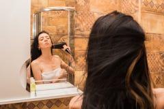 年轻,美丽的妇女在有吹风机的卫生间里干毛发 库存照片
