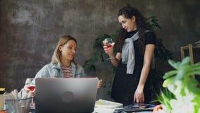 年轻enterpreneurs通过使玻璃叮当响和喝酒庆祝项目成功的精整  妇女是 股票录像
