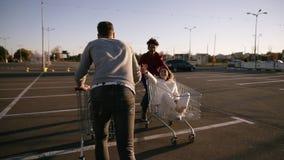 年轻millennials人民赛跑与手推车的-愉快的疯狂的朋友获得与台车的乐趣在停车场 女孩 股票录像