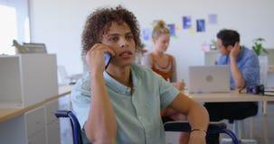 年轻mixed-race残疾男性执行委员谈话与他的手机在办公室4k 影视素材