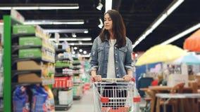 年轻pertty浅黑肤色的男人在大型超级市场走并且推挤去买食物和看的购物台车 股票录像