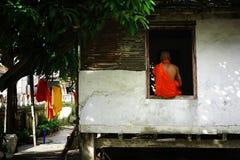 年轻theravada和尚坐在修道院宿舍的窗架 免版税库存照片