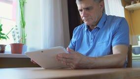 年迈的人在家坐并且使用一台白色片剂个人计算机 库存图片