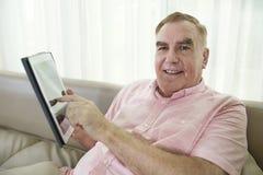 年迈的人坐有片剂的沙发 免版税库存图片