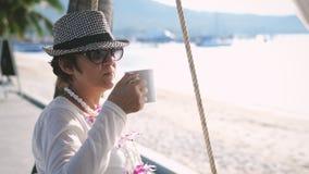 年迈的休息的妇女喝在摇摆的咖啡在美丽的海滩 图库摄影