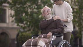年迈的哀伤的残疾男性在轮椅覆盖物少女手,家庭支持上 免版税库存照片