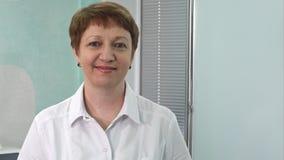 年迈的女性医生画象看照相机微笑的医院走廊的 免版税库存照片