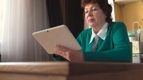 年迈的妇女在家使用一张白色片剂个人计算机-侧视图 图库摄影