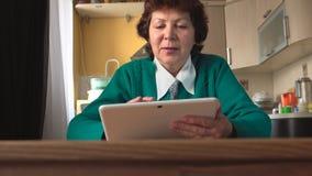 年迈的妇女在家使用一张白色片剂个人计算机-正面图 免版税库存图片