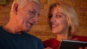 年迈的愉快的夫妇特写镜头射击使用片剂的坐一起休息户内在一栋舒适公寓的沙发 股票视频