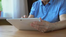 年迈的男性递在一台白色片剂个人计算机的类型在桌上-侧视图 库存照片