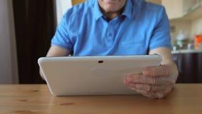 年迈的男性递在一台白色片剂个人计算机的类型在桌上-正面图 库存图片