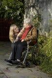 年长下跪在垂直的妇女旁边 免版税库存图片
