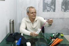 年长人钓鱼竿为钓鱼做准备 免版税库存照片