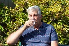年长人饮用水。 图库摄影