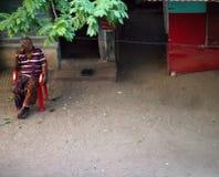 年长印度在一把椅子休息他的家外 免版税库存图片