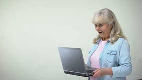 年长夫人惊奇与在膝上型计算机的消息,退休人员的现代技术 股票录像