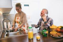 年长夫妇在准备早餐的厨房里 免版税库存图片