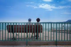 年长夫妇坐一条长凳在看海洋的广场 免版税库存图片