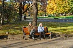 年长夫妇坐长凳在秋天公园Gorkogo在莫斯科 免版税库存图片