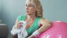 年长女性倾斜在扇动的健身球与毛巾,精疲力尽 股票视频