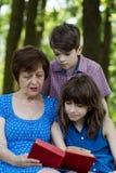 年长妇女、女孩和男孩读一本书反对绿色nat 免版税库存照片