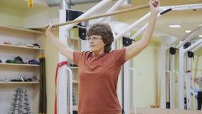 年长妇女举的棍子,做物理疗法行使与在健身屋子里 健康体操 有效的前辈 股票视频
