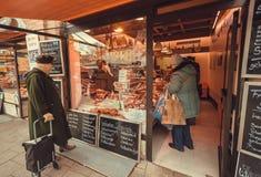 年长妇女买的烟肉和香肠在Viktualienmarkt的肉商店 库存照片