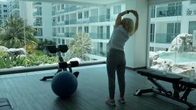 年长妇女做在健身房的squattings 年长妇女资深妇女做在健身房的体育锻炼 免版税库存照片