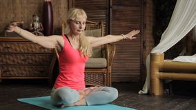 年长妇女做着在菩萨雕象背景的老练瑜伽锻炼 股票视频