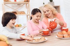 年长妇女和愉快的孙子和孙女在厨房里喝从红色杯子的茶 免版税库存图片