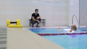 年长妇女在与教练员的游泳池训练 股票录像