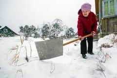 年长妇女在他的农村房子附近清洗雪 图库摄影