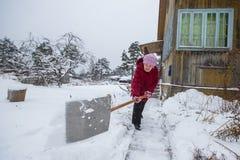 年长妇女在他的家附近清洗雪 图库摄影
