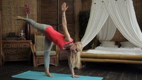 年长妇女在屋子里执行在席子的复杂瑜伽锻炼 股票录像