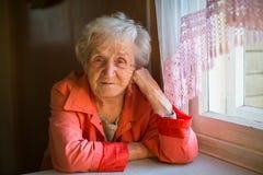 年长妇女在窗口附近的房子里 库存照片