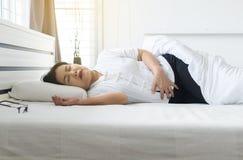 年长妇女有痛苦的stomachache在家,从胃肠痛苦的资深女性痛苦在卧室 免版税库存图片
