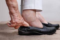 年长妇女胀大投入在鞋子的脚 免版税库存图片