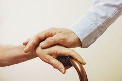 年长疗养所的成熟女性从医院人员护士得到帮助 关闭资深妇女的年迈的起皱纹的手 g 免版税库存图片