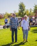 年长站立在草坪和调查距离的男人和妇女 库存照片
